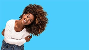 An attractive woman with curly haoir and a bright smile laughing and happy becasue of her orthodontist in Smithtown NY